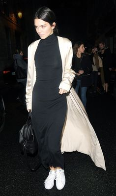 Kendall Jenner wears a black fitted midi dress, a nude silk coat, and white sneakers