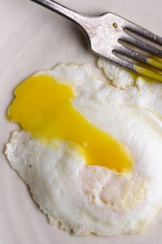 When the bottom of a fried egg is cooked but the yolk still undercooked, use your spatula to gently lift and fold the whites over the yolk from both sides for an over easy egg. (Photo: Karsten Moran for The New York Times)