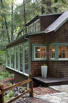 Cottage windows, wood shingles, surrounded by trees.
