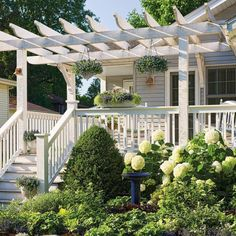 We love how these homeowners dressed up the entrance of their one-story home by adding this fantastic pergola and front porch, painted white to match the trim. Cool blues and whites used in the landscape continue the calming, friendly essence of the space. How about that Incrediball hydrangea out front too?! #PergolaForSaleNearMe