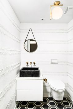 Black and white bathroom with modern mirror and light fixture