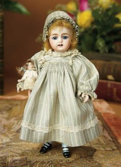 """9""""- German All-Bisque Miniature Doll, 886, by Simon & Halbig w/Square-Cut Teeth~~painted blue above-the-knee stockings, black two-strap heeled shoes. Marks: 886 S 5 H. Comments: Simon and Halbig, circa 1885. Value Points: rare large size, with square-cut teeth, original costume and bonnet, blue painted stockings, and carrying tiny all-bisque miniature doll."""