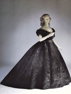 English mourning dress of black watered silk for evening, c. 1861. The neck and sleeves are trimmed with lace and jet.