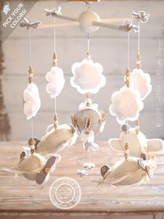 Lovable hanging airplanes hurtling around a hot air ballon surrounded by little clouds. An Airplane Mobile handcrafted from the best Italian fabrics in ivory, white and light grey shades. This is a baby boy mobile perfect for a gender neutral nursery decor. Give special little friends to a special Little One!
