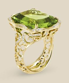 Milgrain etched scrolls curl and climb toward an intense emerald-cut peridot. Delicate in design but substantial in size, the 18K gold filigree sparkles with white diamonds. Diamond info: 115-RD 0.40, 01-PER(NE) 21.32 Fits center stone size EM: 18x16 Center stone not included.