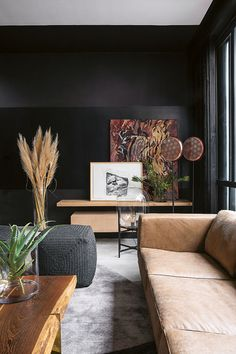 Black walls allowartworks from Smith Gallery to pop. The different textures ofa leather sofa from Klooftique, a wooden coffee table with brass legs from OKHA and punched-copper floor lamps from Weylandts create interest.