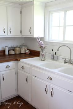 white cabs, wood counters and I love the sink with built in drainboards
