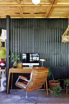 Escritorio entre rústico y moderno, con pared con revestimiento de chapa negra, sillón Eames y escritorio tipo escandinavo en una casa moderna en un country.