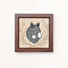 Hand-cut black bear portrait and branches in fawn, pale yellow, light brown, and black. Background is white paper. Set in a dark walnut frame.