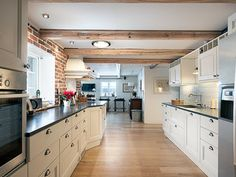 Many likes in this kitchen, the tile wall, the cabinet doors and the handles, plus the wooden beams in the ceiling