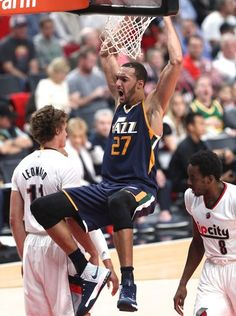 Rudy Gobert hangs on the rim after finishing a dunk.