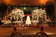 WARNING - TAKE NOTE! Huge flower arrangements dwarf a cake and make it seem insignificant, no matter how beautifully decorated.