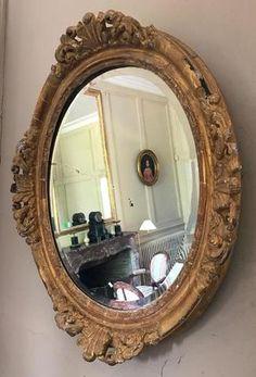 Miroir ovale en bois et stuc doré à décor de palmettes flanquées