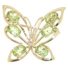 Crafted of 14-karat yellow gold, this charming butterfly-shaped brooch showcases oval-cut checkerboard peridot gemstones and glittering white diamond accents. Two bails allow this pin to be worn as a pendant on your favorite chain or cord.