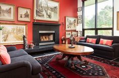 Living Room:23 Enchanting Red Living Rooms: With Magic Red Accent Additions Burgundy Red Carpet Oval Wooden Coffee Table Comfy Gray Couch Red Cushions Bright Red Wall Gold Framed Wall Art Black Marble Fireplace Mantel Large Glass Window Table Lamp In Red Living Room
