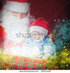Christmas baby wearing a Santa Claus hat and Santa opening a present and gift box! Night, xmas eve, surprise. Magical light. Right there is a place for text. Copy space. Design