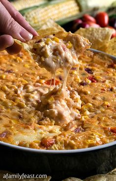 Southwestern Cheesy Corn Dip - Seriously, the best dip we've ever had!  Creamy, warm and cheesy with fresh corn kernels, diced tomatoes and seasonings.  YUM!