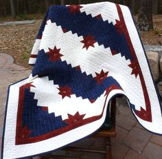 """""""Western Stars"""" is a large lap quilt (45"""" by 59"""") in patriotic red, white, and blue and worked in the Colorado Stars pattern."""