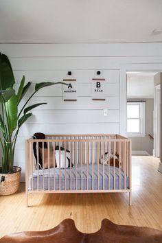 modèle de lit bebe fille ou garçon dans une chambre bébé aménagée en style bohème chic avec murs et plancher de bois et une plante exotique