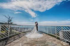 Loving the light-filled blue sky, breathtaking view, and the Bride's elegant long train!