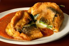 """Chiles Rellenos en caldillo de jitomate"" (Cheese Stuffed Poblano Peppers in Tomato Sauce)."
