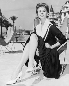 1955:  Italian actress Sophia Loren sits outdoors in a butterfly chair on the beach at Cannes, wearing a dark dress with a pleated skirt and white high heels.  (Photo by Hulton Archive/Getty Images)
