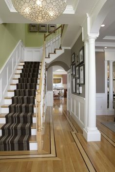 Wainscotting and white stair risers with crown molding and pillars--good ideas for front hall and living room