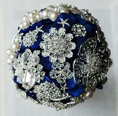 This vintage style bouquet features dark royal blue flowers and silver rhinestone/pearl brooches, with stunning rhinestone brooch and loose pearl beads on the handle. Description from polyvore.com. I searched for this on bing.com/images