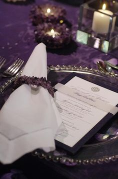 A white menu is backed with dark purple paper and wrapped in a bellyband serving as guests' place cards.