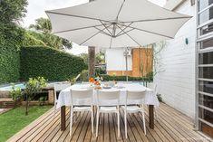Jardim de casa modernista tem mesa para refeição no deck de madeira.