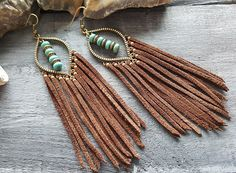 Leather fringe earrings. Brown leather earrings. Bronze bohemian earrings. Boho tassel earrings. Long leather earrings. Turquoise and bronze earrings.  Materials: genuine suede leather,bronze metal,gemstone beads,metal beds. Length with hooks: 12 cm (4.75) Color:bronze,brown,turquoise.  If you have any questions, please contact me. You can view more items in my shop: https://www.etsy.com/uk/shop/VelmaJewelry  Join me on facebook: https://www.facebook.com&#x2...