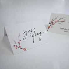 Cherry Blossom Wedding Place Card made of white care stock. Printed on both sides are cherry blossom branches, complete with bright pink flowers that have yellow centers. One side can be personalized while the other side is left blank for you to write your guests' names.