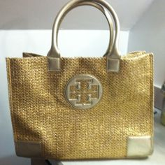 """Tory burch large Ella tote in gold Woven straw gold metallic bag. Leather handles and trim. Bag was used about three times in the summer. Like new condition. Large tote with snaps on the side to make smaller. Beautiful bag. No trades. price is firm. This bag is in """"like new"""" condition. It is a well sort after bag. 16 1/2 inches wide 13 inches in height. Strap drop is 7 1/2 inches  only slight rubbing on leather on bottom leather only noticeable in certain lighting. No marks on the inside…"""