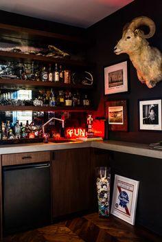 "Dark home bar with neon ""fun"" sign"