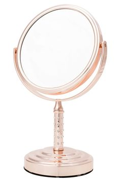 This elegant rose-gold mirror aids in the daily skin care and makeup application rituals.