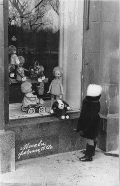 У витрины.Девочка и куклы.