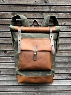 This backpack is made from heavy weight waxed canvas in the color olive green with an outside pocket made in oiled leather.(color of the leather is hazelnut) I made it into an everyday backpack/rucksack, with waxed canvas padded straps. Roll to close top, and outside pocket with protective flap made in oiled leather. The bottom of this bag is also made in oiled leather.. The bag closes with roll to close system and snaps with a waxed leather strap. This rucksack is fully lined with a blue...