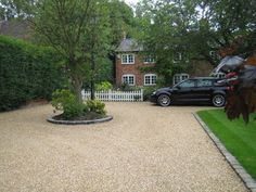gravel driveway with stone cobble edged lawn and central tree. White picket fencing separates the drive from a English cottage garden in front of this 200 year old cottage. From a design by Sue Davis of outside-.
