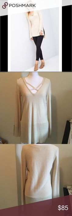 NWT Free People Criss cross Tunic sweater Color is Beige/khaki. Crisscrossing straps at the neckline add intriguing dimension to a supersoft mixed-knit sweater finished with a side-split high/low hem. Arms have slit as well on each side.  51% rayon, 30% acrylic, 12% nylon, 7% linen. Hand wash cold, dry flat. Free People Sweaters