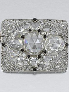 ONYX AND DIAMOND BROOCH, CIRCA 1915. The rectangular plaque to a central oval motif, set with rose-cut diamonds of various shapes, within a radiating frame pierced and millegrain-set with smaller similarly cut stones, accented with cabochon onyx, later brooch fitting.