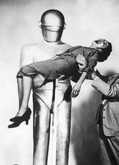 Gort (The Day the Earth Stood Still, 1951) Locke Martin holding up Patricia Neal with the help of a stand. He was big, but not very strong.