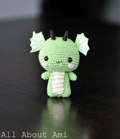 a small green crochet amigurumi dragon