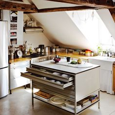 I love the practicality of the island-drawers. And what a wonderful lot of light.