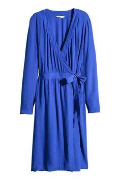 Vestido cruzado en crepé: Vestido en crepé con parte delantera cruzada con cierre oculto. Escote de pico, mangas largas con trabilla y botón, y tira de atar cosida a la cintura. Sin forrar.