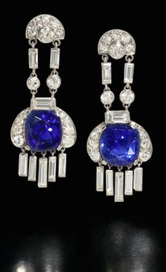 A pair of art deco sapphire and diamond pendent earrings, circa 1930 Each brilliant-cut diamond demi-lune-shaped surmount suspending a cushion-shaped sapphire drop, weighing 6.84 and 6.31 carats, connected by baguette and brilliant-cut diamond connectors, terminating in a baguette-cut diamond tassel, diamonds approximately 3.20 carats total.