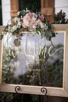 This could say Welcome- Let the Adventure Begin and then have our names and date at the bottom as shown here. Have a white frame with pink and white flowers on top sitting upon a silver easil. #weddingguestbook