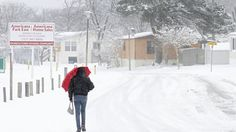 Gwendolyn Lynch walks home from 7-11 down Merry Oaks Drive Thursday morning as a steady snow falls on the area. (Photo by Rob Ostermaier / Daily Press)