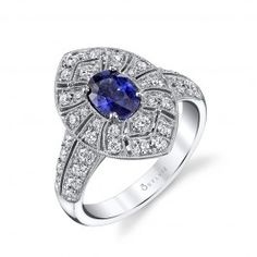 This vintage inspired engagement ring features a dazzling 1.45 carat oval majestic blue sapphire in a prong setting. Geometric sections of glittering diamonds in various sizes with milgrain beaded accents form the marquise shaped halo, encircling the center stone to create an impressive pattern on the crown. The design continues down the tapered band with milgrain accents surrounding graduated sizes of shimmering diamonds. This romantic, antique setting includes a total weight of 2.20…