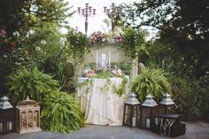 Gorgeous garden wedding inspiration... rustic lanterns, antique candlelabras and a fireplace mantle to top it off.