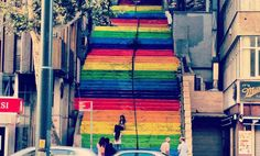 """A Stairway to A Democratic Heaven? Inadvertently these stairs turned into a voice against authoritarianism. """"I didn't do it for a group or as a form of activism. I did it to make people smile,"""" Cetinel told the Turkish media. He had simply tried to beautify his own neighborhood, and he succeeded in doing more than that. The stairs were painted over grey by the gov The next day.  Then instead of Fists shaking in the air. It was colorful paintbrushes to the stares. all over Turkey"""